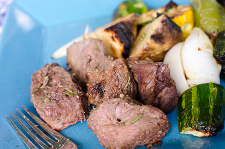 Cooked beef kebabs and grilled organic vegetables
