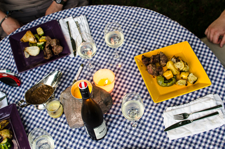 Outdoor dining table with gravy, wine, kebabs